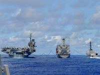 Fuel lines connect USS Kitty Hawk (CV 63), left, and Arleigh Burke-class guided-missile 