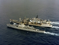 An aerial port quarter view of, front to back: the guided missile cruiser USS LEAHY (CG 16), the oiler USS MISPILLION (AO 105) and the frigate USS SAMPLE (FF 1048) underway, 12/01/1980
