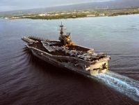 An aerial stern view of the US Navy (USN) Forrestal Class Aircraft Carrier USS RANGER (CV 61), with her Sailors manning the rails and aircraft of the Carrier Air Wing 2 (CVW-2) on her deck, as she arrives at Pearl Harbor Naval Base in Pearl Harbor, Hawaii (HI). In the background is Ford Island.