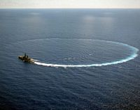 An aerial view of the guided missile cruiser USS REEVES (CG-24) executing a high speed turn. - 1991