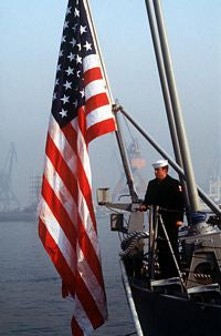 A petty officer stands beside the national ensign on the stern of the guided missile cruiser USS REEVES (CG-24). REEVES is part of the first U.S. Navy warship contingent to visit China in forty years. - 1986 Qingdao China