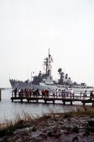 Well-wishers standing on a pier to view the arrival of the aircraft carrier USS SARATOGA (CV-60) battle group watch as the guided missile destroyer USS SAMPSON (DDG-10) passes by. The battle group is returning to Mayport after being deployed in the Persian Gulf<br>March 1991