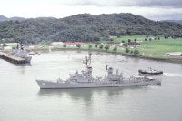 The guided missile destroyer USS SAMPSON (DDG-10), its crew manning the rails, moves past the destroyer USS NICHOLSON (DD-982) as it prepares to dock.