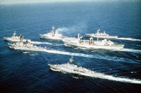 An aerial port beam view of the ships comprising the Standing Naval Force Atlantic underway. The ships are, from top to bottom: HMS DANAE (F-47), HMCS IROQUOIS (DDH-280), HMCS PROTECTEUR (AOR-509), HNLMS VAN NES (F-805), USS SELLERS (DDG-11) and FGS AUGSB