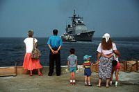 Relatives of crew members aboard the guided missile cruiser USS THOMAS S. GATES (CG-51) watch from the pier as the ship departs for the Persian Gulf in response to Iraq's invasion of Kuwait. - 1990