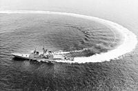 Aerial port beam view of the guided missile cruiser TICONDEROGA (CG-47) performing high speed maneuvers during sea trials. - 1982