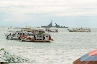 Thai boats anchor in the waters off Pattaya Beach as the guided missile destroyer USS TOWERS (DDG 9) sits on the horizon. The Towers is in Thailand to participate in the joint Thai/US combined exercise THALAY THAI '89.<br>September 1989