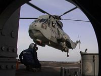 An SH-3 Sea King from Helicopter Support Squadron Two (HC-2) prepares to touch down on the deck of USS Valley Forge (CG 50) to drop off and pick up passengers and cargo. HC-2, Fleet Angels, serves in this capacity throughout the Fifth Fleet area of responsibility as the Desert Ducks. Valley Forge is forward deployed as part of the USS Constellation battle group in support of Operations Enduring Freedom and Southern Watch. 2003