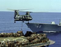 A Helicopter Combat Support Squadron 5 (HC-5) CH-46 Sea Knight helicopter tansports cargo from the helicopter pad of the combat stores ship USS SAN JOSE (AFS-7) during a vertical replenishment operation. The bow of the guided missile cruiser USS VINCENNES (CG-49) is in the background. - 1986