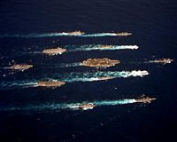 An overhead view of the aircraft carrier USS JOHN F. KENNEDY (CV-67) battle group underway en route to the Mediterranean Sea. The other ships in the group are: the nuclear-powered attack submarines USS ALBUQUERQUE (SSN-706) and USS SEAHORSE (SSN-669); the guided missile cruisers USS GETTYSBURG (CG-64), USS LEYTE GULF (CG-55) and USS WAINWRIGHT (CG-28); the destroyer USS CARON (DD-970); the frigates USS CAPODANNO (FF-1093), USS HALYBURTON (FFG-40) and USS MCINERNEY (FFG-8); the destroyer tender USS PUGET SOUND (AD-38); the ammunition ship USS SANTA BARBARA (AE-28); and the replenishment oiler USS KALAMAZOO (AOR-6). - 1992
