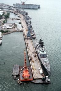A high angle view of a floating dry dock and ships docked at the pier. The docked ships are, from front to rear, the guided missile cruiser USS WILLIAM H. STANDLEY (CG-32), the guided missile destroyer USS HENRY B. WILSON (DDG-7), the guided missile cruiser USS STERETT (CG-31) and the oiler USNS HASSAYAMPA (T-AO-145). - 1981