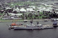 A port beam view of the guided missile cruiser USS WILLIAM H. STANDLEY (CG-32) docked at a pier. - 1981