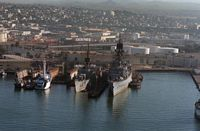 A starboard bow view guided missile cruiser USS WILLIAM H. STANDLEY (CG 32), right, and the guided missile frigate USS SCHOFIELD (FFG 3) moored at a pier. - 1986 Naval Station San Diego