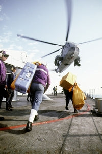 Crew members aboard the guided missile cruiser USS WORDEN (CG-18) prepare to deliver outgoing mail to the aircrew of a Helicopter Combat Support Squadron 2 (HC-2) SH-3 Sea King helicopter during Operation Shield, 05/20/1992