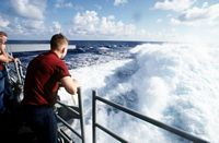 Off duty sailors on the fantail of the guided missile cruiser USS YORKTOWN (CG-48) observe the heavy wake generated by 32 knots of speed as the ship heads for Guantanamo Bay, Cuba after being on station off the coast of Haiti as a part of Operation Support Democracy. - 1993