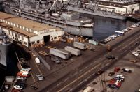 An aerial view of the Naval Supply Center facility at Pier No. 2. The destroyer tender USS YOSEMITE (AD 19) is docked at a pier.<br>- 1983