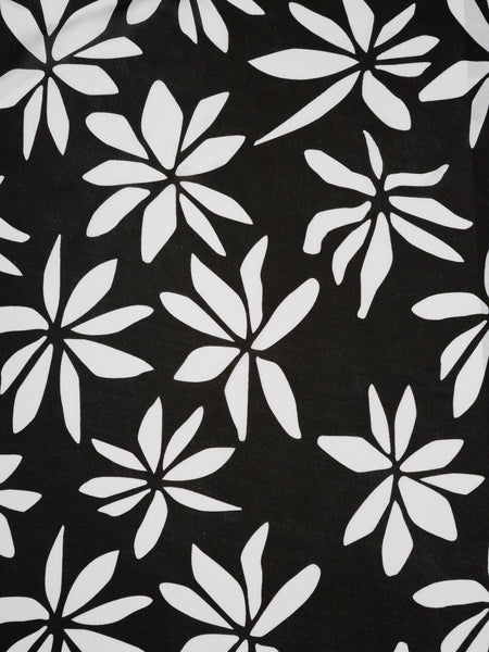 Medium weight cotton jersey. Black background with large banana leaf-style white pattern