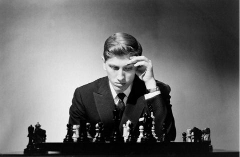 Bobby Fischer playing chess posing with chessboard and chess pieces