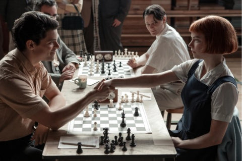 beth harmon winning chess tournament with chess board chess pieces and hand shake