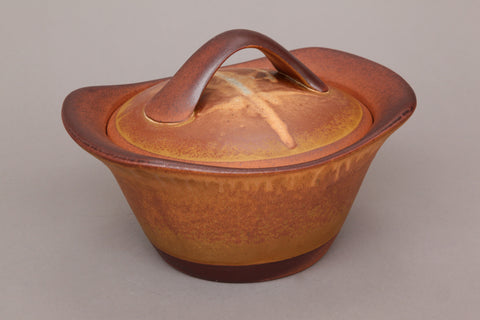 Flameware clay casserole pot in gold color.