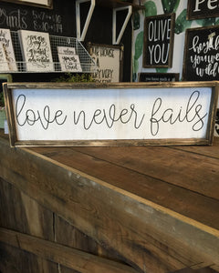 Love Never Fails Cursive Wood Sign