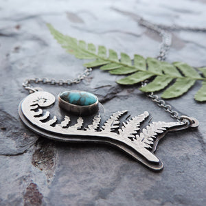 hand cut unfurling fern pendant with turquoise stone