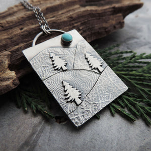 silver pendant with textured mountains and turquoise stone