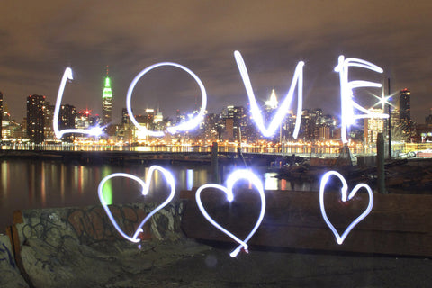 Long exposure of Love and three hearts written with the NYC skyline in the background along the