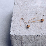 gold plated sterling silver pendulum drop ball earrings by lines and current in matt finish