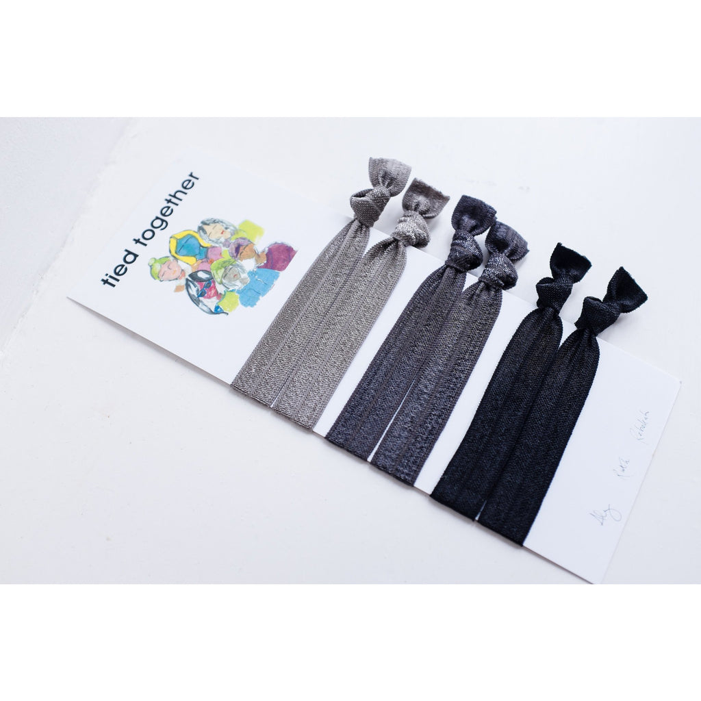 the minimal palette, of black, charcoal and grey hair ties, hair ribbons, hair elastics on a book we designed.