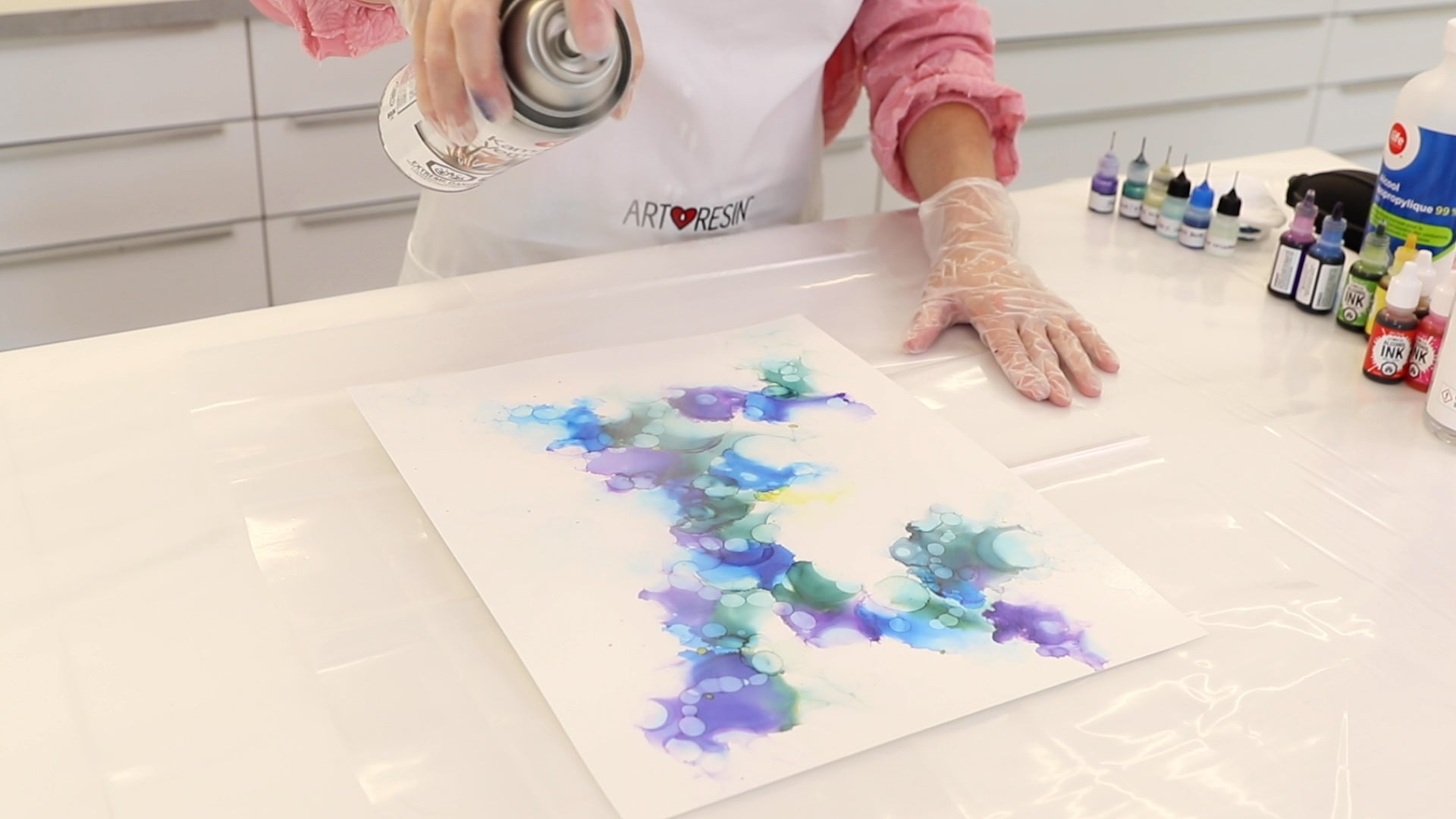 spraying varnish on alcohol ink abstract painting