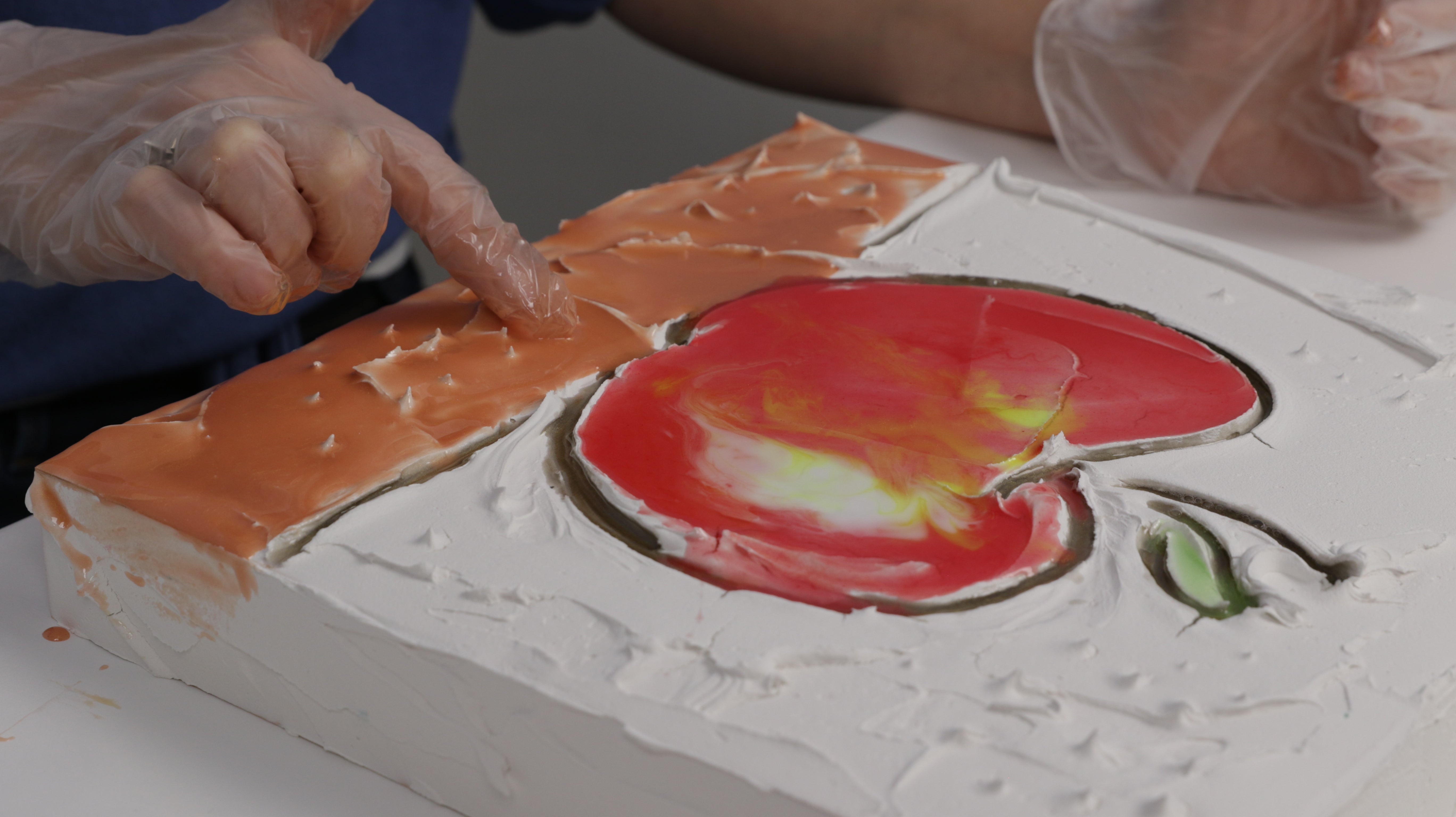 pour tinted resin over artwork using gloved hand to blend