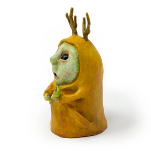Alder, is an one-of-a-kind, hand sculpted and painted sculpture of an antlered forest mystic in a saffron colored robe and offering a leaf sprig.