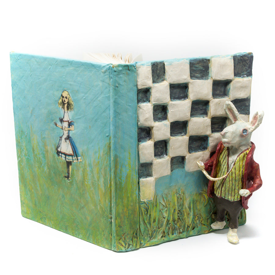One-of-a-kind art, is sculpted on the cover of a reclaimed copy of Alice in Wonderland and Through the Looking Glass Altered Book, written by Lewis Carroll and illustrated by John Tenniel.