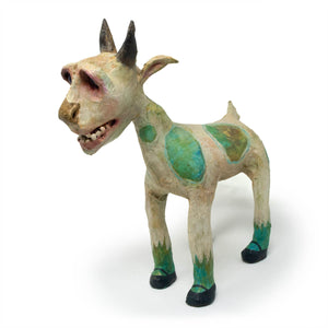 Cloaks is an original, one-of-a-kind, hand-sculpted & painted grungy-white goat with blue and green colored polka-dots, and wearing black maryjane shoes.