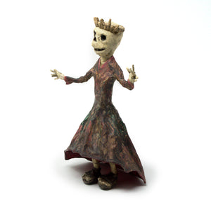 skeleton queen wearing a long, flared, multi-color dress, sandals and her royal crown