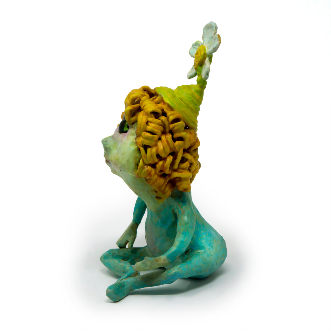 Spring, the Cyclops is an original, one-of-a-kind, hand-sculpted, hand-painted freestanding sculpture of a curly-haired cyclops wearing a blue onsie and a flower hat.
