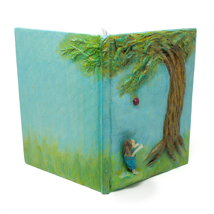 One-of-a-kind art, is sculpted on the cover of a reclaimed copy of The Giving Tree, written and illustrated by Shel Silverstein