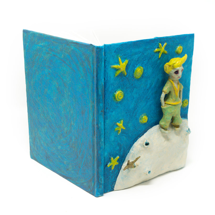 One-of-a-kind art, is sculpted on the cover of a reclaimed copy of The Little Prince, written and illustrated by Antoine de Saint-Exupery