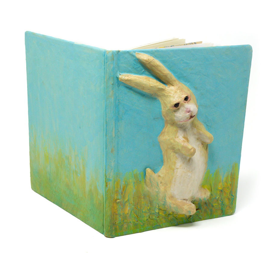 One-of-a-kind art, is sculpted on the cover of a reclaimed copy of The Velveteen Rabbit, written by Margery Williams and illustrated by William Nicholson.