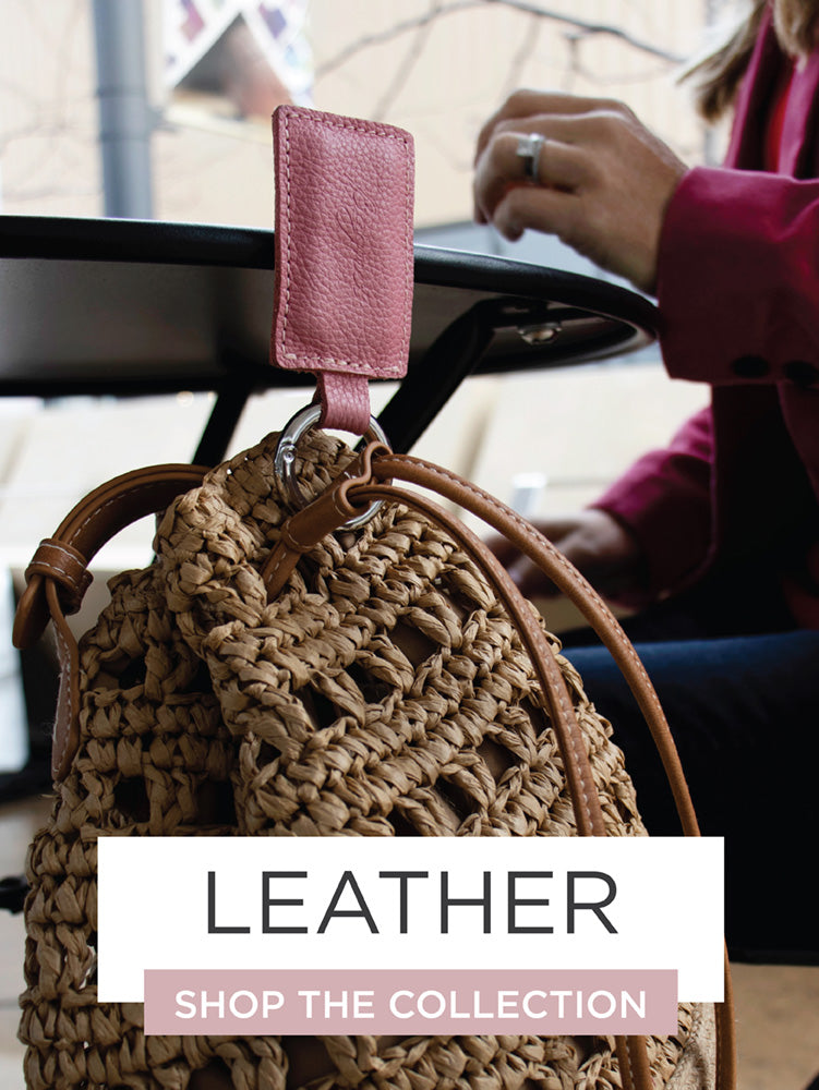 Leather bagnet holding a purse hanging off metal table