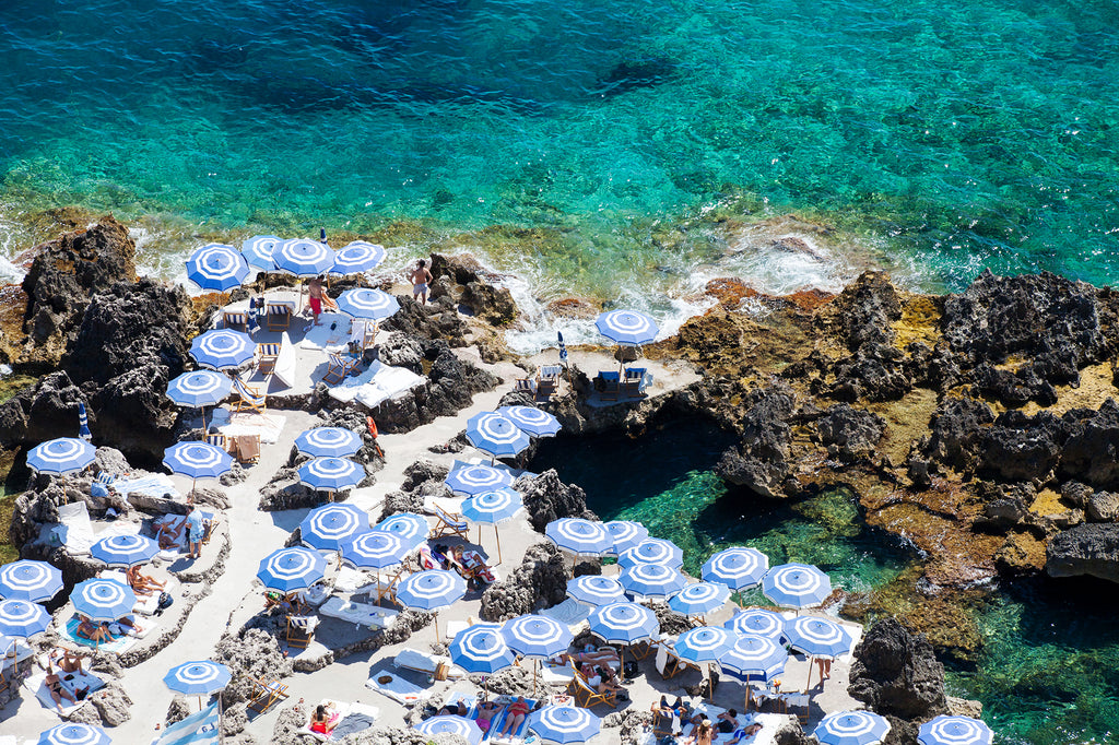La fontelina beach Capri an Italian beach with blue and white umbrellas