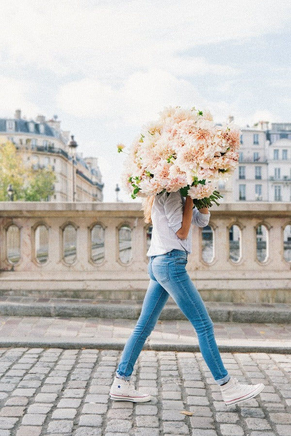 Joyful & Unstoppable is a photo of a girl in Paris in Ile St Louis with the biggest bunch of pink dahlias and is part of a limited edition series named Young Girl in Bloom by photographer Carla Coulson celebrating women loving and believing in themselves and building their self esteem by trusting their intuition.