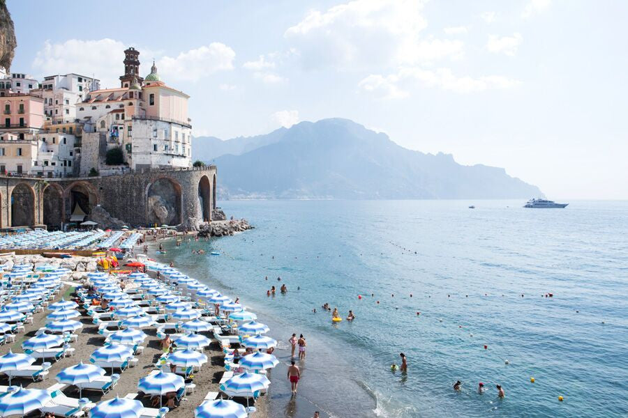 Blue and white beach umbrellas on Atrani beach the amalfi coast by Carla Coulson