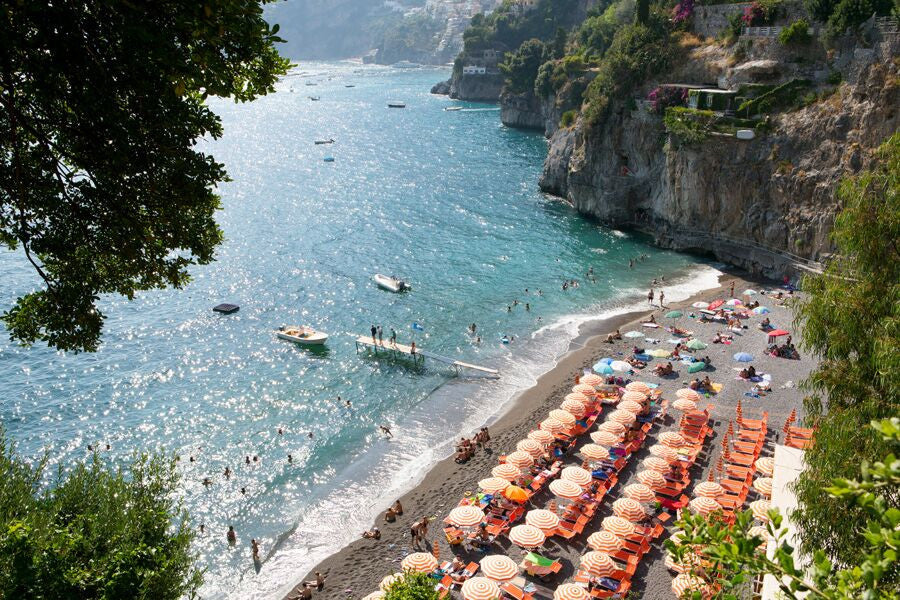 Rows of orange and white umbrellas at the Arienzo beach club on the Amalfi Coast with Positano in the background