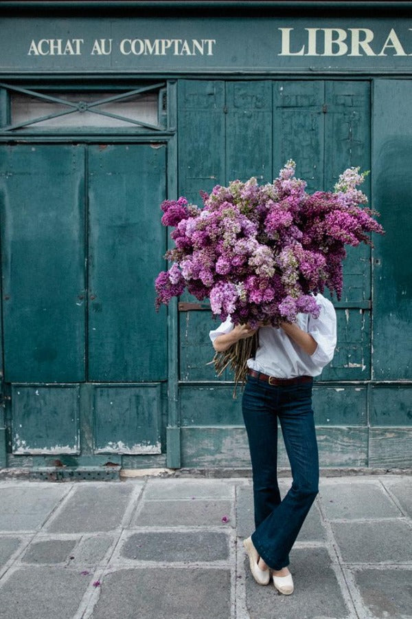 Beauty In Balance is a photo of a girl in St Germain des Prés holding a big bunch of lilacs and is part of a limited edition series named Young Girl in Bloom by photographer Carla Coulson celebrating women loving and believing in themselves and building their self esteem by trusting their intuition.