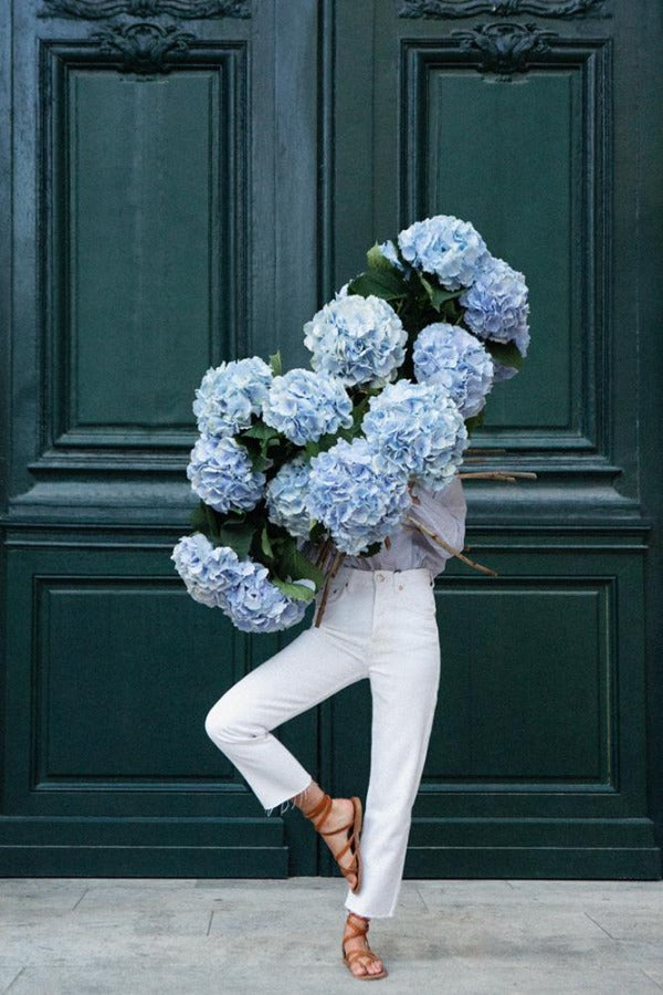Centred In Self is a photo of a young girl in St Germain des Prés holding a giant bouquet of blue hydrangeas standing in a tree pose and is part of a limited edition series named Young Girl in Bloom by photographer Carla Coulson celebrating women loving and believing in themselves and building their self esteem by trusting their intuition.