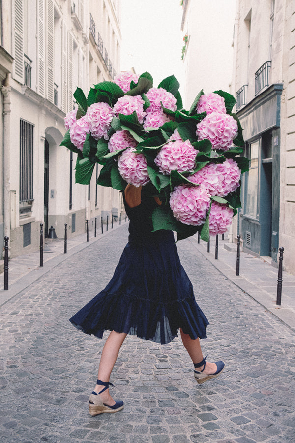 Free and Fearless is a photo of a girl in Paris in St Germain des Prés holding a giant bouquet of pink hydrangeas and is part of a limited edition series named Young Girl in Bloom by photographer Carla Coulson celebrating women loving and believing in themselves and building their self esteem by trusting their intuition.