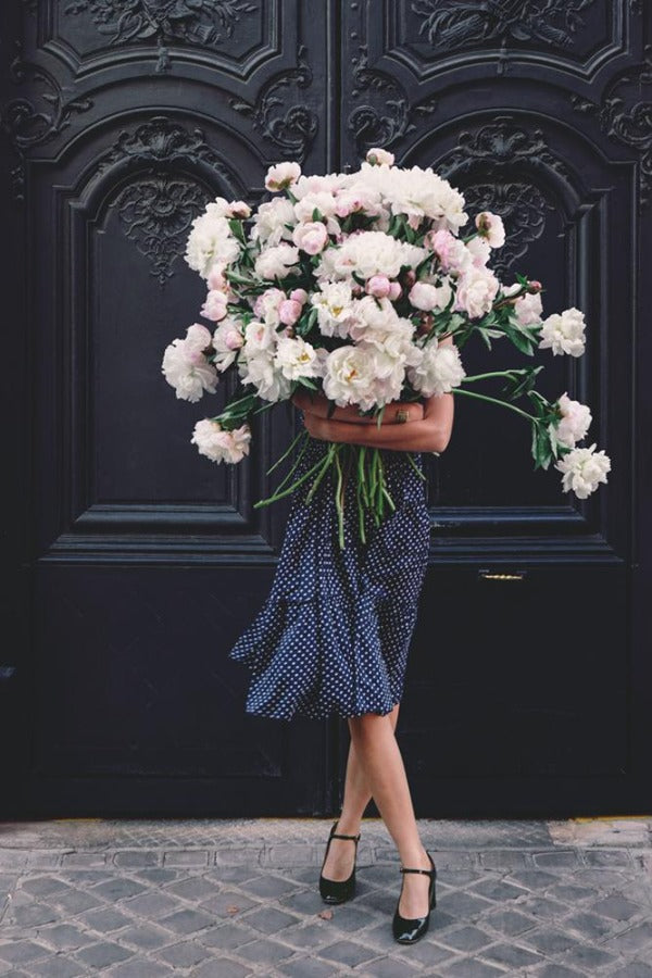 Hold The Faith is a photo of a girl in Paris in St Germain des Prés holding the biggest bunch of ancient white peonies and is part of a limited edition series named Young Girl in Bloom by photographer Carla Coulson celebrating women loving and believing in themselves and building their self esteem by trusting their intuition.