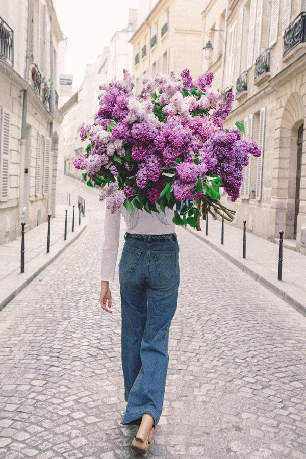 On My Way is a photo of a girl in Paris in St Germain des Prés holding a giant bouquet of lilacs and is part of a limited edition series named Young Girl in Bloom by photographer Carla Coulson celebrating women loving and believing in themselves and building their self esteem by trusting their intuition.